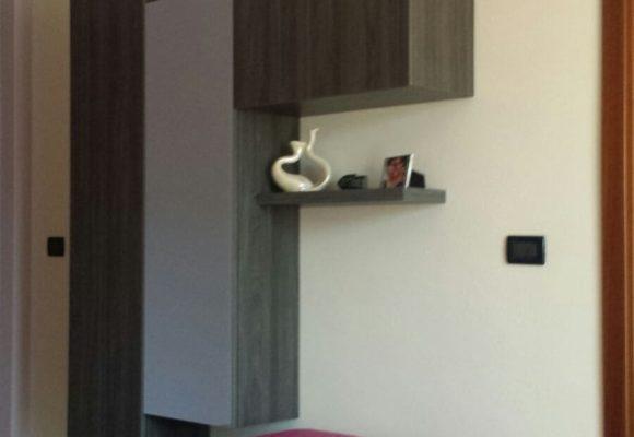 Nella foto e' presente un piccolo soggiorno su misura con ante battenti e a ribalta e specchio