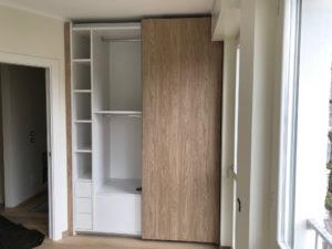 Particolare di un armadio con ante scorrevoli in nicchia ,realizzato in nobilitato noce e bianco